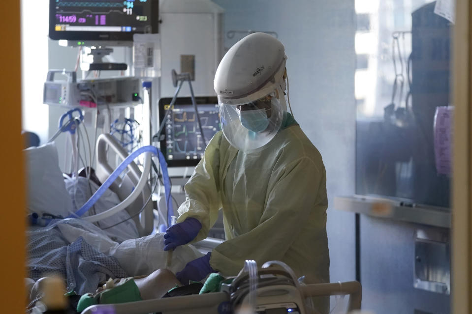 A healthcare worker tends to a COVID-19 patient in the intensive care unit at Santa Clara Valley Medical Center during the coronavirus pandemic in San Jose, Calif., Wednesday, Jan. 13, 2021. (AP Photo/Jeff Chiu)