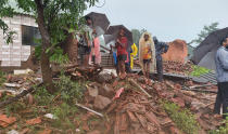 People watch rescue efforts after a landslide in Taliye village, in the western Indian state of Maharashtra, Friday, July 23, 2021. Landslides triggered by heavy monsoon rains hit parts of western India, killing at least 32 people and leading to the overnight rescue of more than 1,000 other people trapped by floodwaters, officials said Friday. (AP Photo)