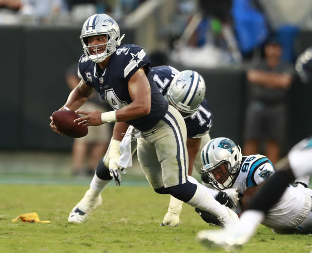 FILE- In this Sunday, Sept. 9, 2018, file photo, Dallas Cowboys' Dak Prescott (4) is sacked by Carolina Panthers' Wes Horton (96) during the second half of an NFL football game in Charlotte, N.C. It's no secret that Prescott and his revamped group of Dallas receivers hold the key to creating consistent running room for Ezekiel Elliott. The formula needs improvement with the Cowboys trying to avoid their first 0-2 start under Jason Garrett. (AP Photo/Jason E. Miczek, File)