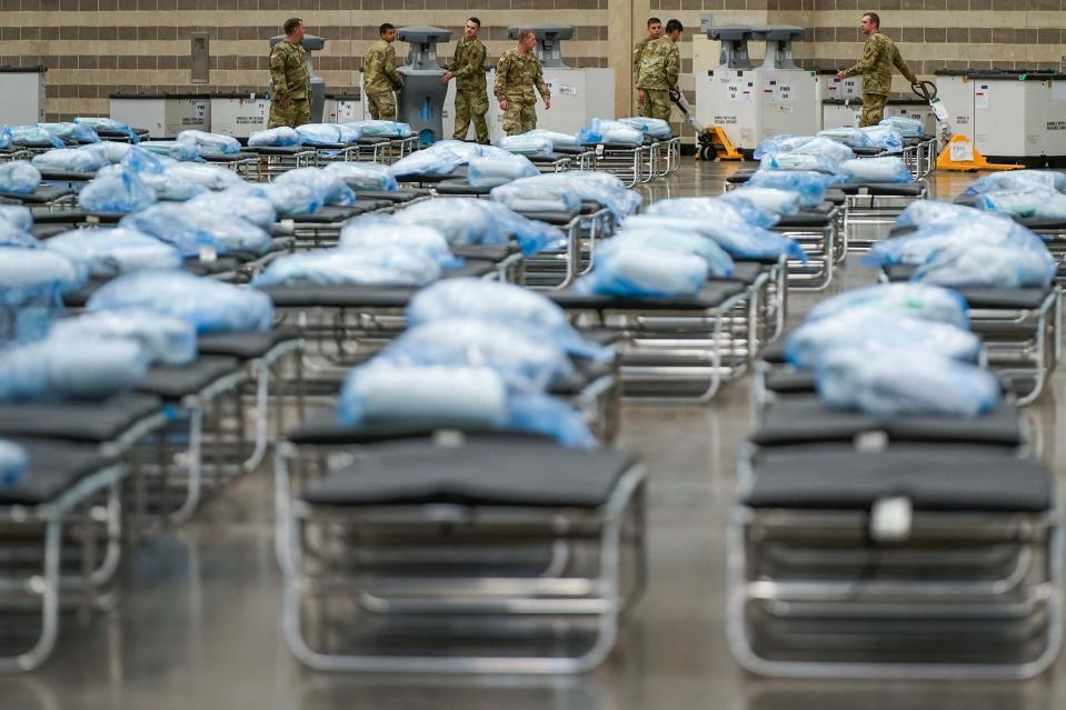 Members of the Texas Army National Guard unpack crates of supplies as they set up a field hospital in response to the new coronavirus pandemic at the Kay Bailey Hutchison Convention Center on Tuesday, March 31, 2020, in Dallas. (Smiley N. Pool/The Dallas Morning News via AP, Pool)
