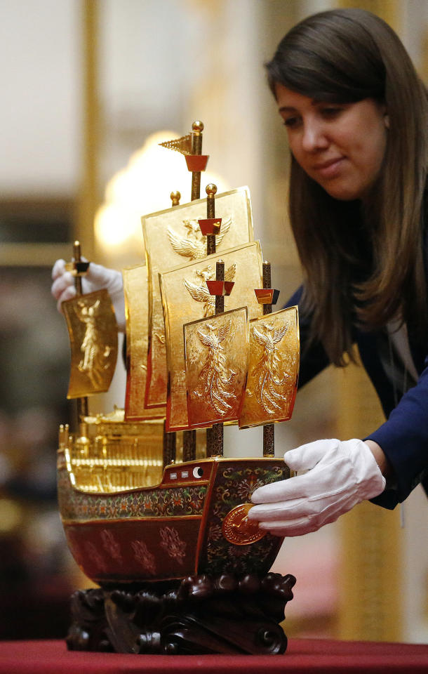 """<p>Hannah Belcher, exhibition coordinator of the Royal Collection Trust, inspects the Vessel of Friendship, a model of the """"treasure ship""""<br /> sailed by the 15th century Chinese navigator Zeng He, that was presented by Chinese President Xi Jinping in 2015, at Buckingham Palace in London, Monday, April 3, 2017. (Frank Augstein/AP) </p>"""
