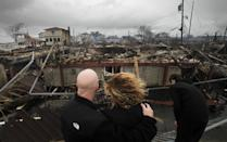 Robert Connolly, left, embraces his wife Laura as they survey the remains of the home owned by her parents that burned to the ground in the Breezy Point section of New York, Tuesday, Oct. 30, 2012. More than 50 homes were destroyed in the fire which swept through the oceanfront community during superstorm Sandy. At right is their son, Kyle. (AP Photo/Mark Lennihan)