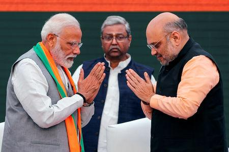 FILE PHOTO: Indian Prime Minister Narendra Modi and chief of India's ruling Bharatiya Janata Party (BJP) Amit Shah, greet each other before releasing their party's election manifesto for the April/May general election in New Delhi, India, April 8, 2019. REUTERS/Adnan Abidi/File Photo