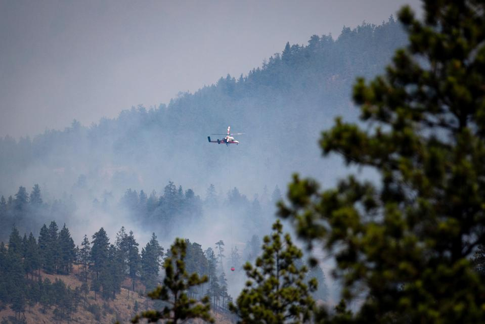 A helicopter prepares to drop water on a wildfire burning in Lytton (The Canadian Press via AP)