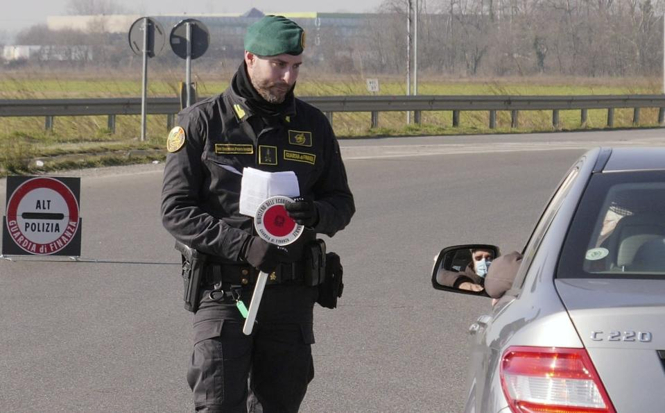 An Italian tax police officer talks to a man wearing a sanitary mask at a road block set in Casalpusterlengo, Northern Italy, Monday, Feb. 24, 2020. Italy scrambled to check the spread of Europe's first major outbreak of the new viral disease amid rapidly rising numbers of infections and a third death. Road blocks were set up in at least some of 10 towns in Lombardy at the epicenter of the outbreak, including in Casalpusterlengo, to keep people from leaving or arriving. (AP Photo/Paolo Santalucia)