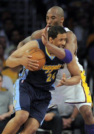 Los Angeles Lakers shooting guard Kobe Bryant, right, fouls Denver Nuggets point guard Andre Miller as he drives to the basket during the first half of an NBA first-round playoff basketball game, Sunday, April 29, 2012, in Los Angeles. (AP Photo/Mark J. Terrill)