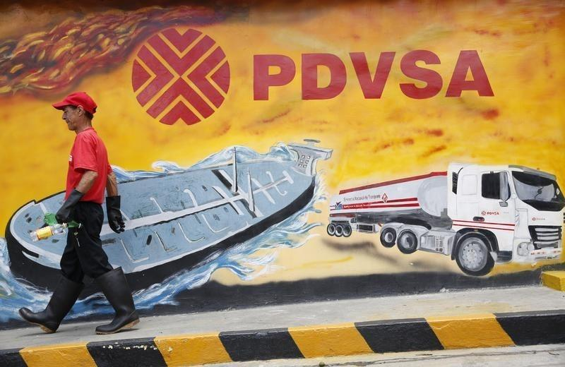 A worker walks past a mural with a PDVSA logo at its gas station in Caracas