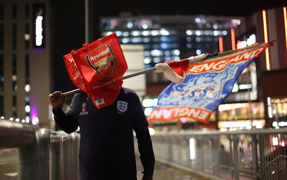 An England fan with a Arsenal bag over his head outside the stadium before the match - REUTERS/Carl Recine