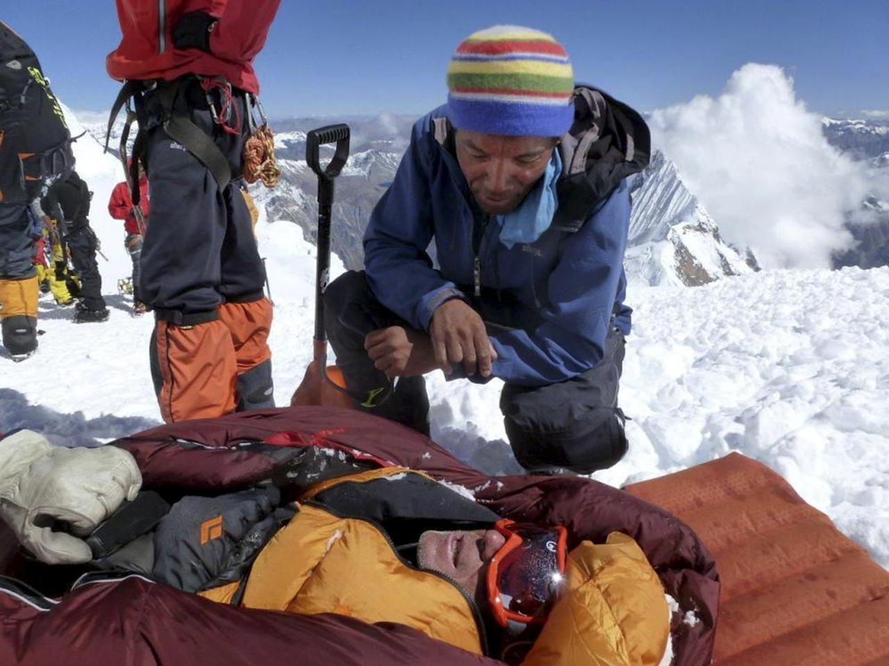 In this picture taken Sunday, Sept. 23, 2012 and released by Alpine Ascents International, an unidentified rescuer speaks to an unidentified survivor in the debris field of an avalanche on Mount Manaslu in northern Nepal. Rescue helicopters flew over the high slopes of the northern Nepal peak again Monday to search for climbers lost in an avalanche that killed at least nine mountaineers and injured others. Many of the climbers were French, German and Italian. (AP Photo/Garrett Madison, Alpine Ascents International)
