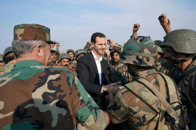 Syrian soldiers cheer President Bashar al-Assad during his visit to the southern outskirts of rebel-held Idlib province in the country's northwest