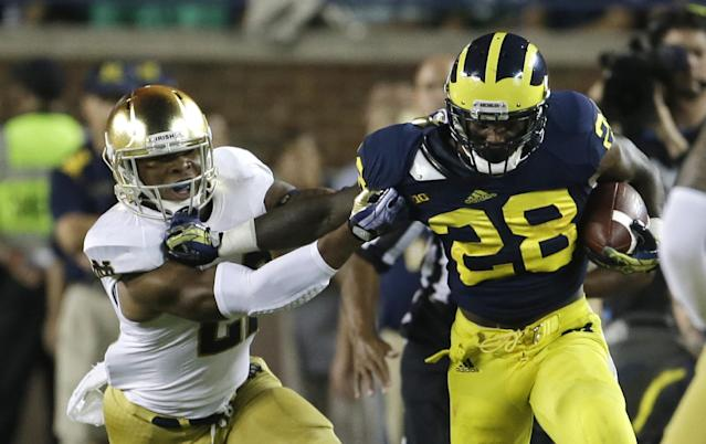 Michigan running back Fitzgerald Toussaint (28) pulls away from Notre Dame safety Elijah Shumate for a first down during the first quarter of an NCAA college football game in Ann Arbor, Mich., Saturday, Sept. 7, 2013. (AP Photo/Carlos Osorio)