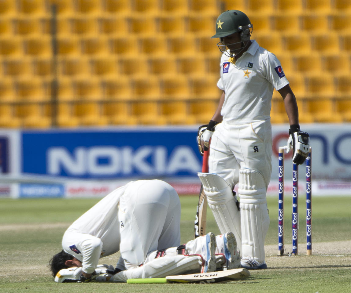 Pakistan's Captain Misbah-ul Haq (down) celebrates his century together with fellow batsman Adnan Akmal on the third day of their first Test against South Africa at the Sheikh Zayed Cricket Stadium in Abu Dhabi on October 16, 2013. Pakistan's pace-cum-spin attack caught world number one Test team South Africa napping on the third day of the first Test in Abu Dhabi.  AFP PHOTO/STR        (Photo credit should read STR/AFP/Getty Images)