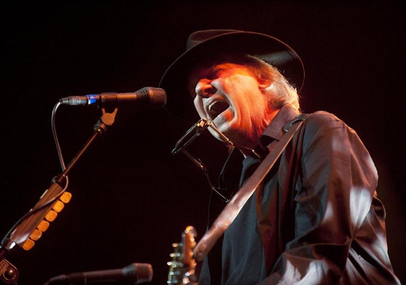 "FILE - In this May 14, 2012 file photo originally provided by Robin Hood, musician Neil Young performs onstage at the Robin Hood Annual Benefit, Monday, May 14, 2012, at the Javits Center in New York. Young, whose memoir ""Waging Heavy Peace"" due out in October, will be interviewed by fellow singer Patti Smith at BookExpo America in New York this week. (AP Photo/Courtesy Robin Hood, file)"
