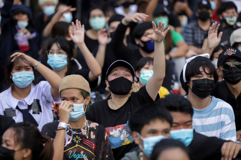 Pro-democracy protesters use hand signals during an anti-government protest in Bangkok