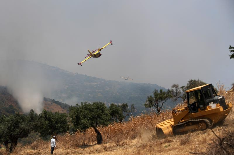 Airplanes operate over a fire in the village of Gavalas, on the Greek island of Evia, Friday, July 5, 2019. Greek authorities say four villages were evacuated overnight on the island of Evia after two new brush fires broke out several hours after a major blaze led to the mobilization of more than 100 firefighters and the evacuation of another village. (AP Photo/Thanassis Stavrakis)