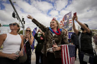 Heidi Forte, middle, with other supporters of President Donald Trump wait for the motorcade on the road to Mar-a-Lago, Trump's Palm Beach estate, on Wednesday, Jan. 20, 2021, in West Palm Beach, Fla. (AP Photo/Lynne Sladky)