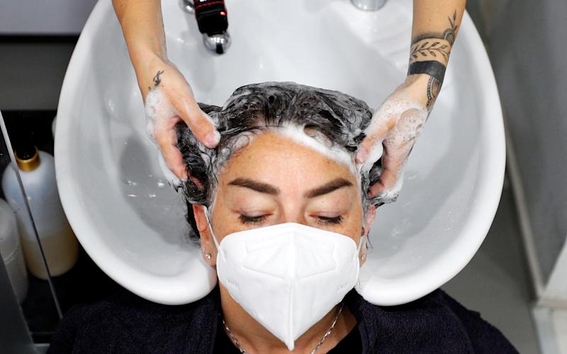 A customer wearing a protective mask has her hair washed at a beauty salon in Rome - GUGLIELMO MANGIAPANE/REUTERS