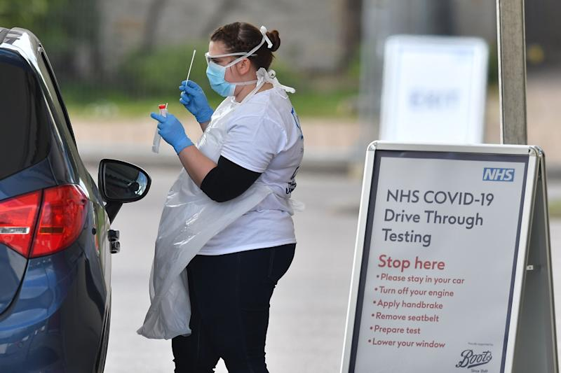 NHS workers are swabbed at a drive-in facility to test for the novel coronavirus COVID-19, set up in the carpark of Chessington World of Adventures in Chessington, Greater London on April 3, 2020. (Photo by Ben STANSALL / AFP) (Photo by BEN STANSALL/AFP via Getty Images)