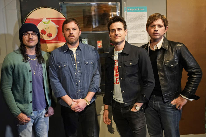 Rockers Kings of Leon, from left, Nathan, Caleb, Jared, and Matthew Followill, pose for a photo in front of their exhibit at the Rock and Roll Hall of Fame Thursday, April 29, 2021, in Cleveland. The band toured a new digital exhibit at the Rock and Roll Hall of Fame for the NFT (non-fungible token) launching before the rock band plays at the NFL draft, Thursday, April 29, 2021, in Cleveland. from left, Nathan, Caleb, Jared, and Matthew Followill are shown. (AP Photo/Tony Dejak)