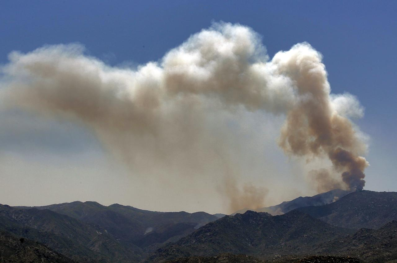 A smoke column rises Monday, May 14, 2012 near Crown King, Ariz. Fire crews spent the weekend fighting several wildfires including the four and a half square mile blaze near Crown King. (AP Photo/Matt York)