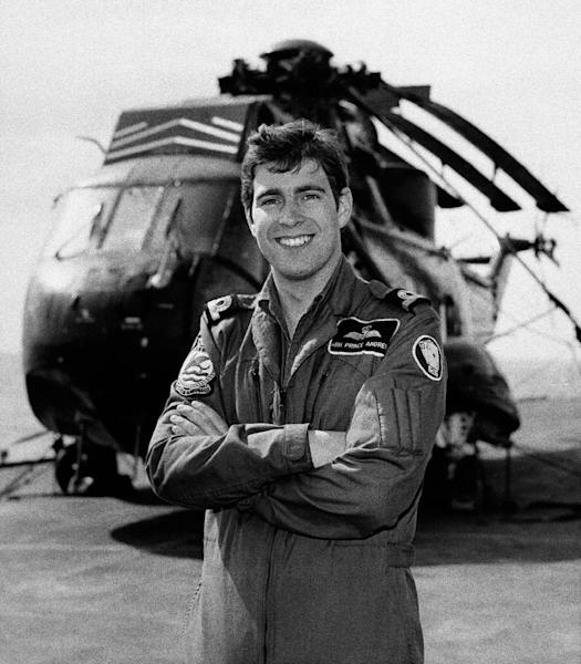 FILE - In this Nov. 1982 file photo, Britain's Prince Andrew, then a sub-Lieutenant at the Royal Naval Air Station, poses for a photograph in front of a RAF Sea King helicopter, Culdrose, Cornwall, England. Military service is a tradition for the men of Britain's royal family, but combat has been off-limits for the next in line of succession. (AP Photo, File)