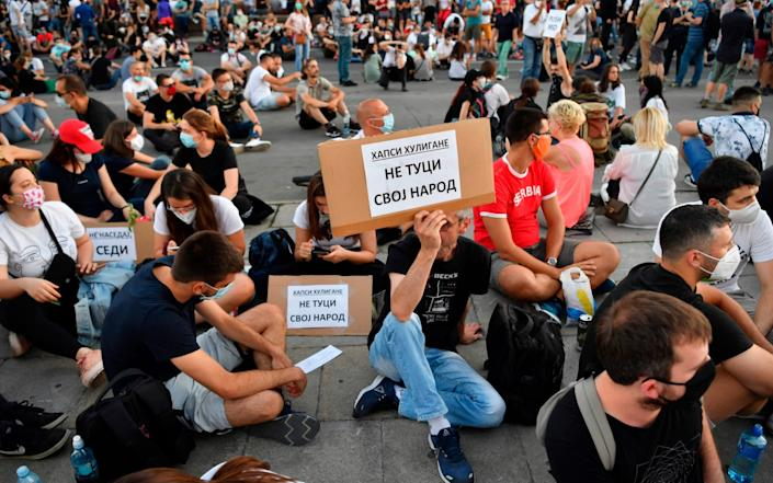 """People sit holding placards reading """"Don't beat your own people"""" or """"Arrest hooligans"""" during the protest in Belgrade - Andrej Isakovic/AFP"""