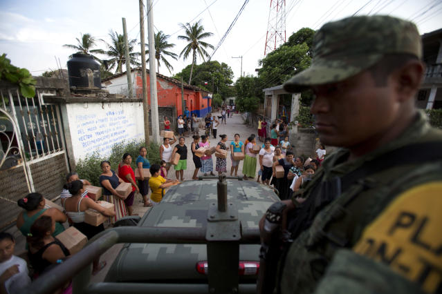 <p>A soldier looks on as housewives stand in line for rations and water in Juchitan, Oaxaca state, Mexico, a zone heavily affected by Thursday's magnitude 8.1 earthquake, Saturday, Sept. 9, 2017. The boxes contained a mix of common Mexican household dried goods, including beans, corn flour, rice, powdered milk, tuna, hot chocolate, and and either jalapeno peppers or spicy sauce. (AP Photo/Rebecca Blackwell) </p>