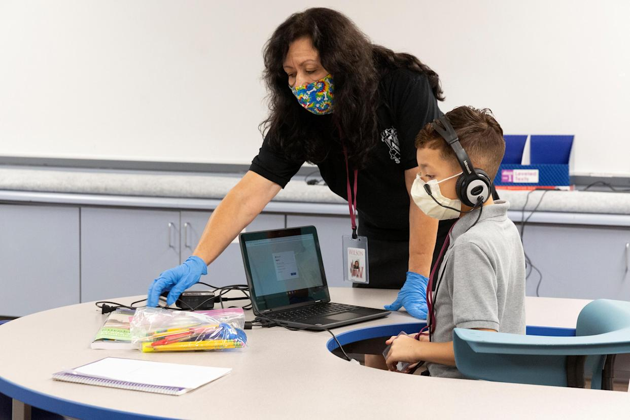 An instructional assistant helps a student as in-person learning resumes with restrictions to prevent the spread of COVID-19 at Wilson Primary School in Phoenix. (Reuters/Cheney Orr)