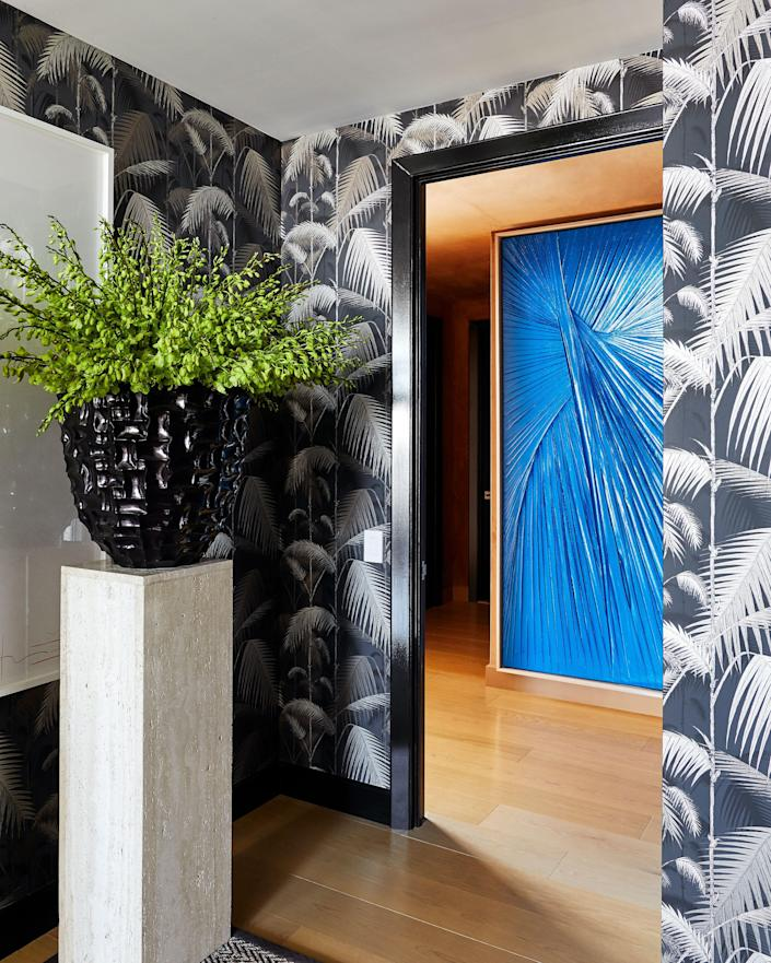 """A large painting of draped fabric by Matthew Chambers sits in the couple's bedroom's entranceway. """"I fell in love with it because I studied clothing design, and it reminds me of a Madame Gres dress—something kneaded and gorgeous. It's actually painted in car paint, so while it's delicate it's also really tough,"""" says Atwood."""