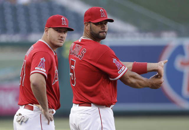 Los Angeles Angels' Albert Pujols, right, stretches next to teammate Mike Trout before the team's baseball game against the Seattle Mariners on Saturday, July 13, 2019, in Anaheim, Calif. (AP Photo/Marcio Jose Sanchez)