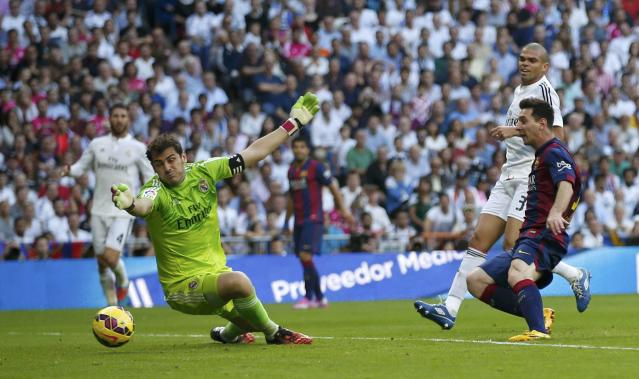 "Barcelona's Lionel Messi (R) tries to score against Real Madrid's goalkeeper Iker Cassillas during their Spanish first division ""Clasico"" soccer match at the Santiago Bernabeu stadium in Madrid October 25, 2014. REUTERS/Sergio Perez (SPAIN - Tags: SOCCER SPORT)"
