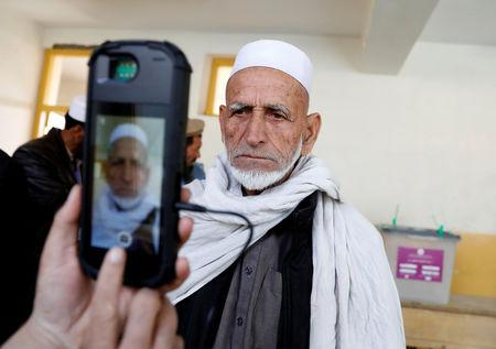 An election official scans a voter's eye with a biometric device at a polling station during a parliamentary election in Kabul, Afghanistan, October 20, 2018. REUTERS/Mohammad Ismail