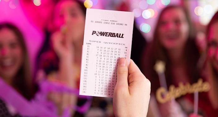 A woman holds a winning Powerball ticket.