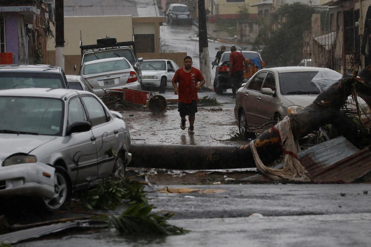 A man runs on the street next to debris and damaged in Guayama.