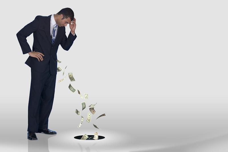 Guy in a suit watching money fall out of his pocket and into a hole in the floor.