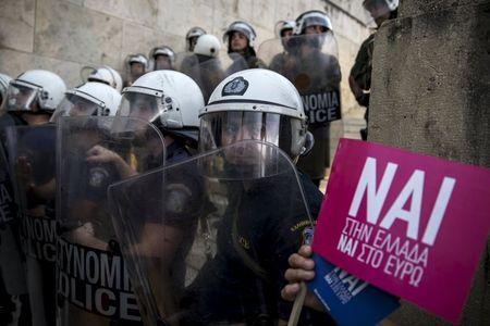 """Riot policemen stand guard next to a small flag with the word """"Yes"""" in Greek during a rally in front of the parliament building in Athens, Greece, June 30, 2015. REUTERS/Marko Djurica"""