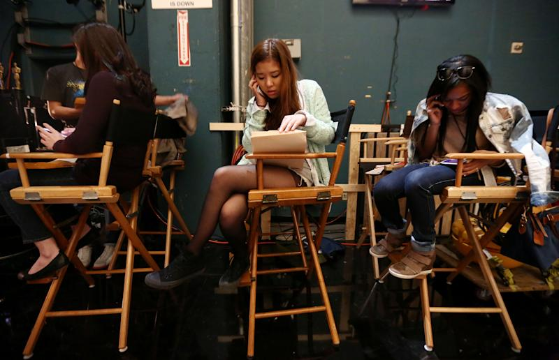 Hearin Ko, 19, from Seoul, South Korea, center, and ChaRon Brabham, 20, from New York, sit backstage during rehearsals for the 85th Academy Awards in Los Angeles, Wednesday, Feb. 20, 2013. Ko and Brabham were among the six college students selected to serve as trophy presenters for The Academy Awards which will take place on Sunday, Feb. 24, 2013. (Photo by Matt Sayles/Invision/AP)