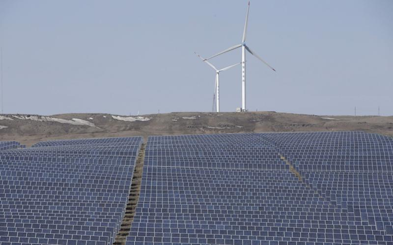 Solar panels and wind turbines - Credit: Reuters