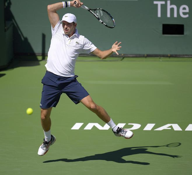 Julien Benneteau, of France, volleys with Novak Djokovic, of Serbia, in their quarterfinal match at the BNP Paribas Open tennis tournament, Friday, March 14, 2014, in Indian Wells, Calif. (AP Photo/Mark J. Terrill)