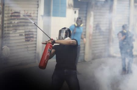 A protester fires an iron rod with a homemade weapon at riot police clashes in the village of Bilad Al Qadeem, south of Manama, January 5, 2015. REUTERS/ Hamad I Mohammed