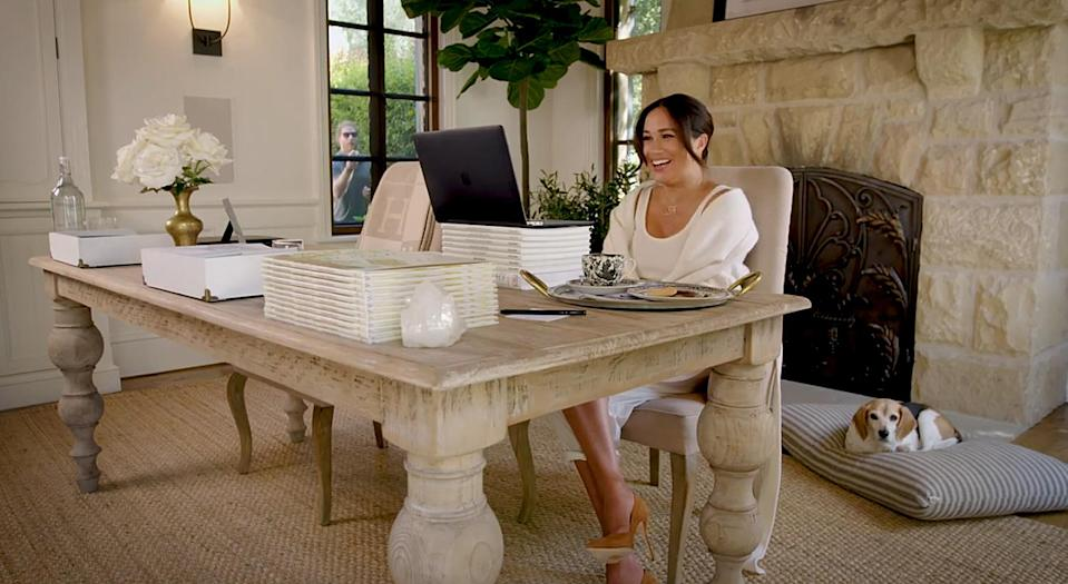 """<p><a href=""""https://people.com/tag/meghan-markle/"""" rel=""""nofollow noopener"""" target=""""_blank"""" data-ylk=""""slk:Meghan Markle"""" class=""""link rapid-noclick-resp"""">Meghan Markle</a>'s 40x40 initiative video announcement on her birthday gave royal watchers a glimpse into her <a href=""""https://people.com/royals/prince-harry-juggles-cameo-meghan-markle-40th-birthday-video-first-glimpse-baby-lilibet-diana/"""" rel=""""nofollow noopener"""" target=""""_blank"""" data-ylk=""""slk:sunny home office"""" class=""""link rapid-noclick-resp"""">sunny home office</a>. Eagle-eyed fans may recall that the duchess has <a href=""""https://people.com/royals/meghan-markle-celebrates-anniversary-smart-works-clothing-line/"""" rel=""""nofollow noopener"""" target=""""_blank"""" data-ylk=""""slk:appeared on video calls"""" class=""""link rapid-noclick-resp"""">appeared on video calls</a> in the space before, but this is the most we've seen of the space, which features homey accents such as a large, table-style desk, fresh-cut flowers, a healing crystal, a cozy stone fireplace and plenty of copies of Meghan's <em>New York Times</em> bestseller <a href=""""https://www.google.com/search?q=the+bench+inspired+by+father%27s+day+poem+people.com&oq=the+bench+inspired&aqs=chrome.0.69i59j69i57.2096j0j7&sourceid=chrome&ie=UTF-8"""" rel=""""nofollow noopener"""" target=""""_blank"""" data-ylk=""""slk:The Bench"""" class=""""link rapid-noclick-resp""""><em>The Bench</em></a>, which was inspired by a Father's Day poem she wrote for Harry. Naturally, there's also a designated """"workspace"""" for the real boss of the place — their beagle, Guy!</p>"""