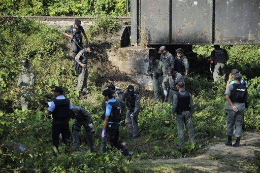 Thai bomb squad members inspect the site of a bomb blast