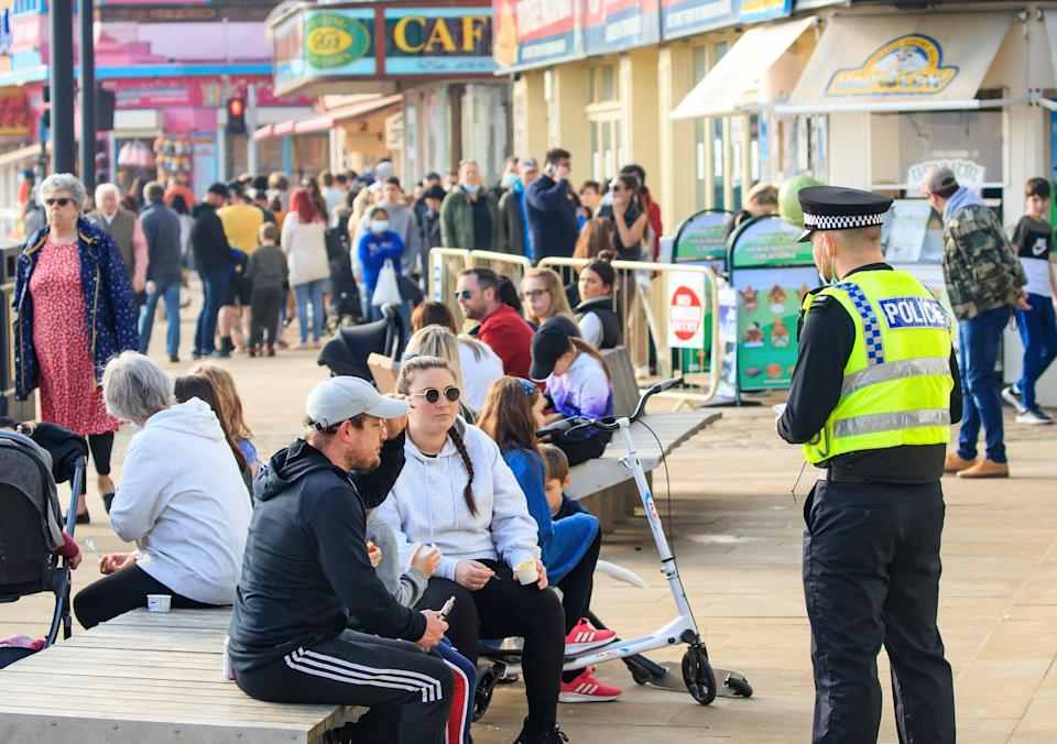 A police officer speaks to people in Scarborough, North Yorkshire, during England's third national lockdown to curb the spread of coronavirus. Picture date: Sunday February 28, 2021.