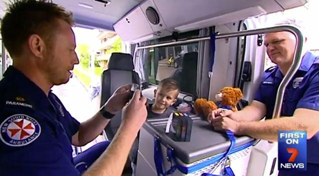 Lawson Lowe with the two paramedics who helped change his memory of ambulances following a horrific accident. Photo: 7 News