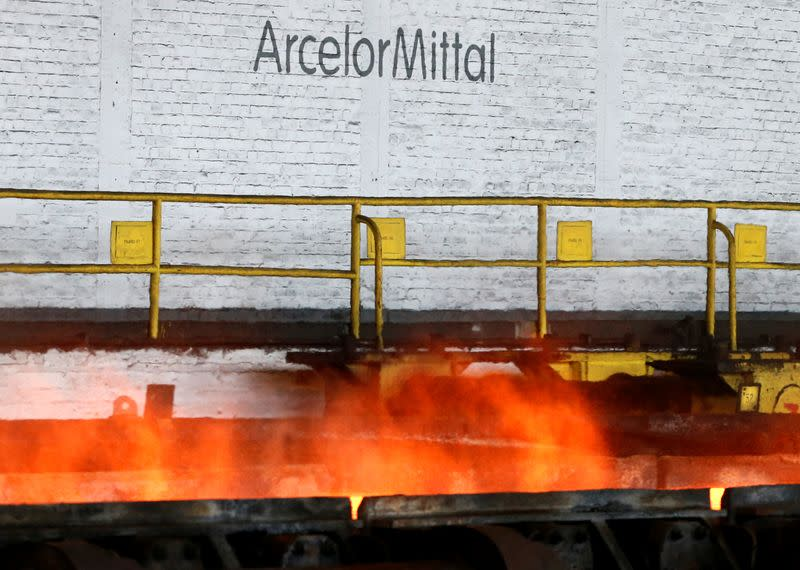 The logo of ArcelorMittal is pictured in front of heat rising from a red-hot steel plate at the ArcelorMittal steel plant in Ghent