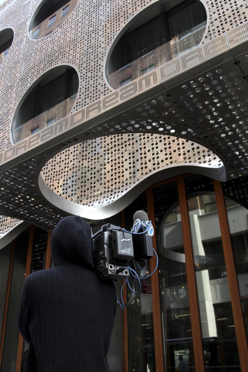 A camera man films in front of the Dream Hotel in New York, Wednesday, Sept. 19, 2012. Lindsay Lohan was arrested in New York early Wednesday on charges that she clipped a pedestrian with her car and did not stop, police said. The 26-year-old actress was arrested at 2:25 a.m. as she left a nightclub at the Dream Hotel on 16th Street in Manhattan's Chelsea neighborhood, police said. They said no alcohol was involved. Lohan was charged with leaving the scene of an accident and causing injury. She was given a ticket and will have to appear in court at a later date. (AP Photo/Seth Wenig)