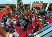 Families wait in line to meet Santa Claus at Fashion Centre at Pentagon City, decorated for the holidays, in Arlington, Virginia