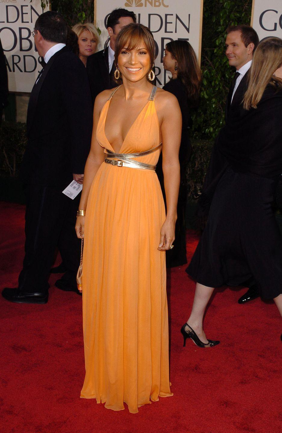 <p>In 2004, J. Lo was a ray of sunshine in this plunging Michael Kors dress featuring a gold belt cinched at the waist.</p>