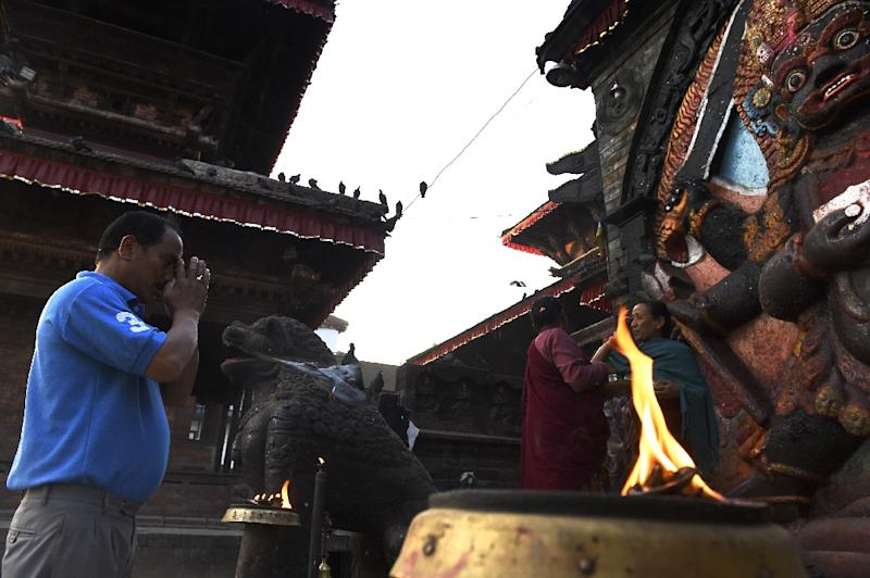 A Hindu devotee offers prayers in front of a statue of Hindu diety Kaal Bhairab in the Durbar Square neighbourhood of Kathmandu, on May 2, 2015 (AFP Photo/Roberto Schmidt)