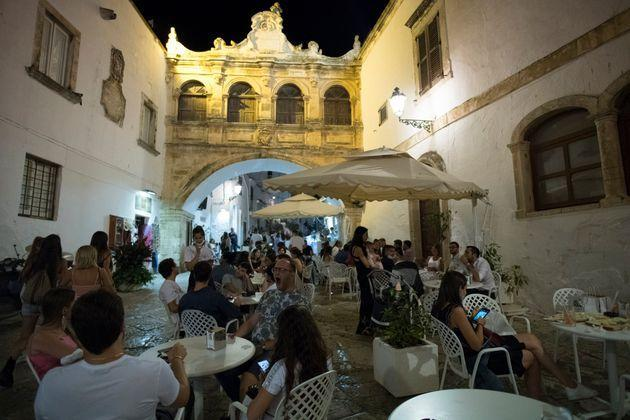 OSTUNI, ITALY - AUGUST 12: General view of people wearing protective masks sitting in the dehor of a restaurant in Piazza Beato Giovanni Paolo II in the Ostuni nightlife on August 12, 2020 in Ostuni, Italy. Tourism in the Puglia Region was very active in the summer on the beaches, towns and clubs of the city center, despite the danger of Covid 19, Italians and tourists in general respected the Covid-19 prevention measures. (Photo by Stefano Guidi/Getty Images) (Photo: Stefano Guidi via Getty Images)